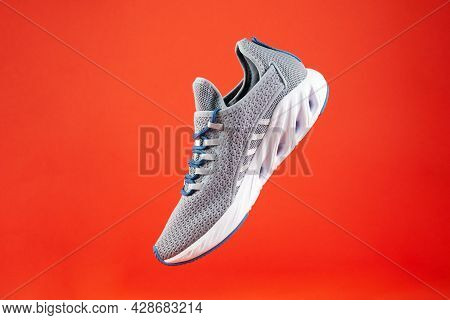 Stability And Cushion Running Shoes. New Unbranded Running Sneaker Or Trainer On Orange Background.