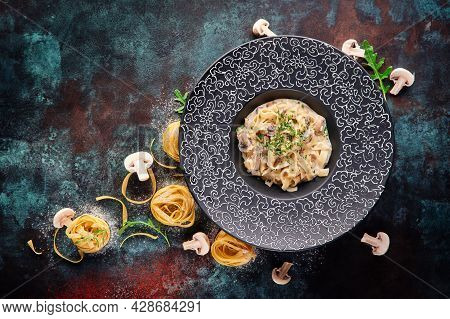 Traditional Tagliatelle Pasta With Mushrooms In A Creamy Sauce In A Black Plate On A Blue Oxidized B