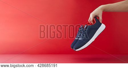 Hand Hold Sports Shoes On A Red Background. Holding New Fashion Sneakers For Running. Choosing And B