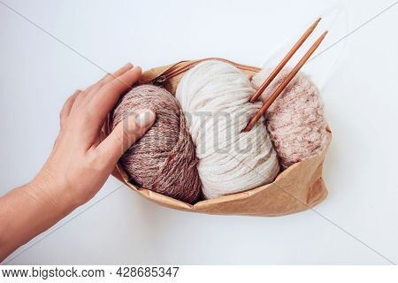 Woman's Hand Holds A Craft Eco Bag With Skeins Of Yarn In Nude Colors And Knitting Needles On A Whit