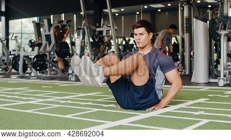 Handsome Young Asian Guy Lying On Exercise Doing Sit-ups Fat Burning Workout In Fitness Class. Athle