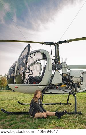 Tween Girl Sitting On Green Grass Of Flying Field Near Helicopter