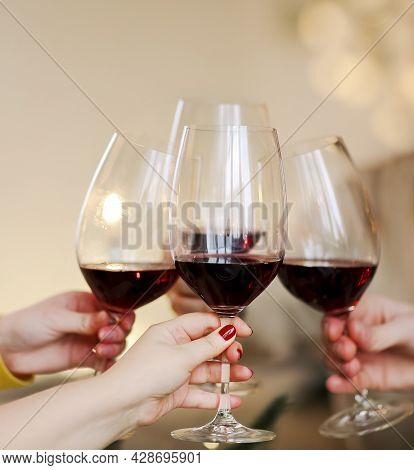 Group Of Anonymous People Clinking Wineglasses And Proposing Toast During Party. Celebration And Hol