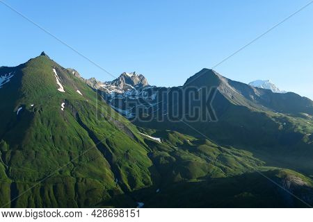 Famous Mont Blanc Mountain In The Background. Snowcapped Mountain Top Behind An Alpine Slope With Gr