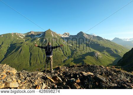 A Man From Behind, Facing The Mountain In Summer. Hiker Standing With Arms Outstretched Up To The Sk