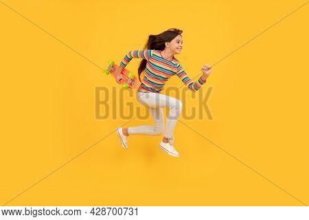 Happy Energetic Teen Girl Skateboarder Jumping With Penny Board Skateboard, Pennyboard