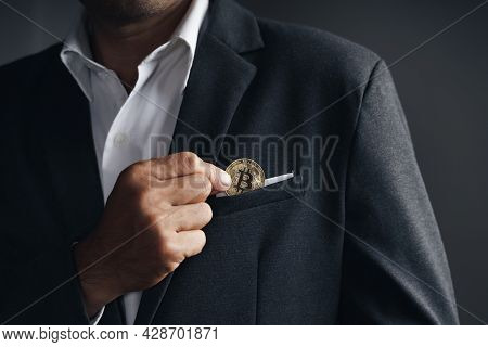 Handsome Investor Businessman Put A Golden Bitcoin To The Suit Pocket On Dark Background, Trading, C