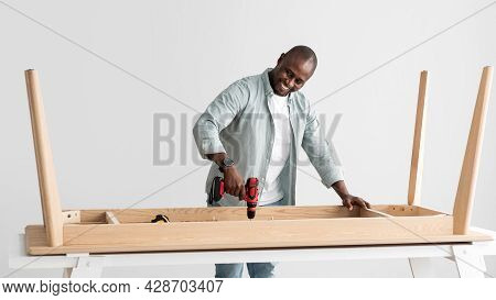Happy African American Handyman Drilling Wooden Planks Of Table, Assembling New Furniture With Elect