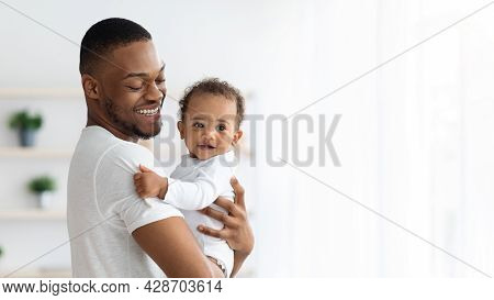 Father And Baby. Portrait Of Happy Black Millennial Dad Holding Infant Child In Arms