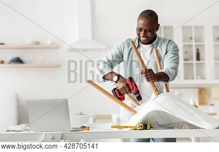 Online Lesson For Assembling Furniture With Own Hands. African American Man Collecting Chair And Loo