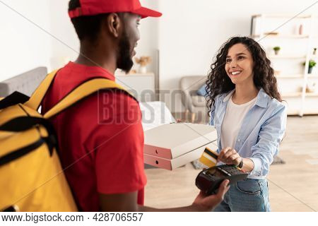 Smiling Deliveryman Holding Pos Machine, Woman Paying With Bankcard
