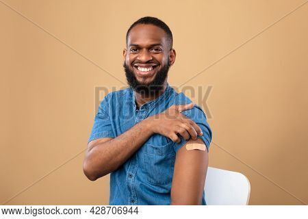 Happy Vaccinated Black Man Showing Shoulder With Band Aid After Coronavirus Vaccine Shot, Posing Aft