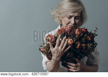 Sad Elderly Woman Touching Bouquet Of Withered Rose Flowers. Gray Haired Mature Lady In Depression.