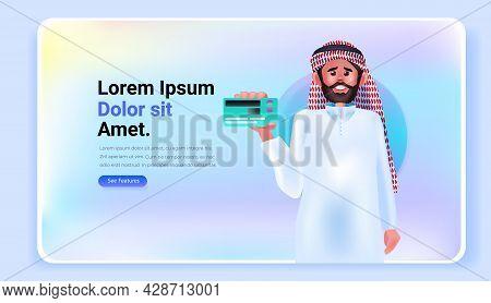 Arab Man Holding Debit Or Credit Card Electronic Wireless Payment Digital Transaction Online Shoppin