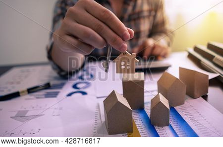 Realtor Agent Showing House Key With Home Miniature Model, House Design Document, Price Of House, Ca