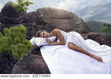 A Beautiful Young Girl Is Sleeping On The Rocks In The Mountains, A Snow-white Bed, Pillow And Sheet