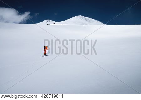 A Young Sportsman Skier In An Orange Suit Climbs A Ski Tour On A Snow-covered Slope To Mount Elbrus.