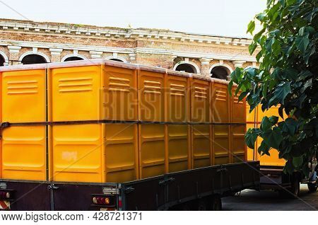 Truck Transporting Mobile Or Portable Toilets. Yellow Cabines Of Bio Toilets In The City Center. Wc