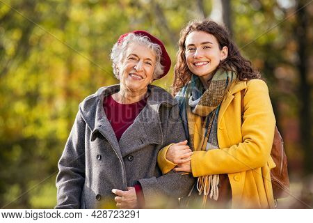 Portrait of senior woman in park walking with smiling granddaughter. Old grandmother walking with lovely granddaughter in autumn park with copy space. Mother and smiling daughter looking at camera.
