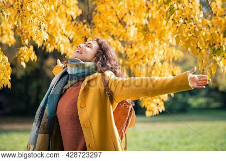 Beautiful young woman relaxing at park during autumn season with closed eyes. Happy free natural girl breathing deeply in park with foliage in background. Pretty woman expressing freedom outdoor.