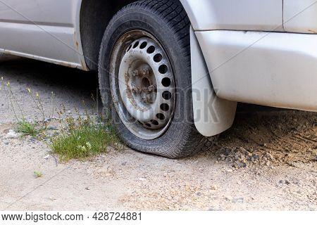 A Deflated Wheel On A Car Close Up