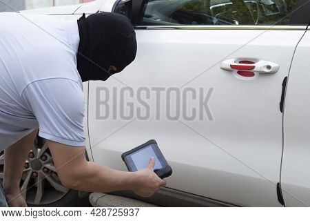 Car Theft. The Hijacker Is Trying To Steal A Car In The Parking Lot.