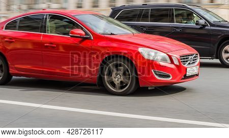 Two Usual Cars Racing At High Speed On City Road With Motion Blur. Red Volvo S60 In Motion, Front Si