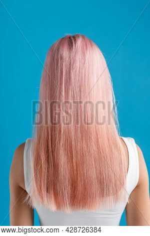 Beautiful Sleek Natural Long Pink Color Dyed Hair Of Young Woman Standing Isolated Over Blue Studio