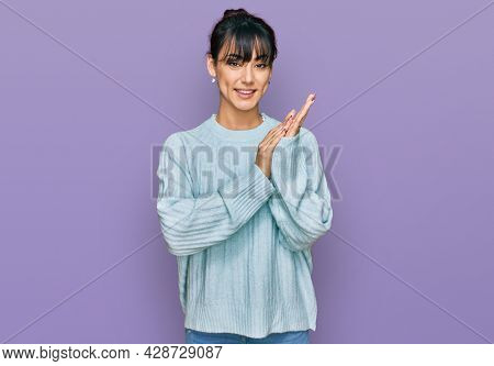 Young hispanic woman wearing casual clothes clapping and applauding happy and joyful, smiling proud hands together