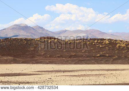 Lava Rocks On A Hillside Ridge Surrounding Sand Dunes Taken At A Volcanic Field In Fossil Falls, Ca
