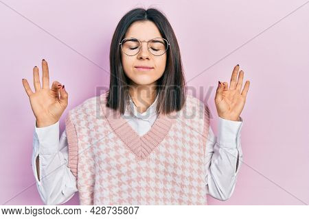 Young brunette woman wearing elegant sweater and glasses relax and smiling with eyes closed doing meditation gesture with fingers. yoga concept.