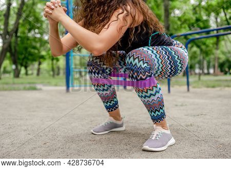 Girl with elastic rubber band doing squats outdoors. Young woman during workout with sport equipment