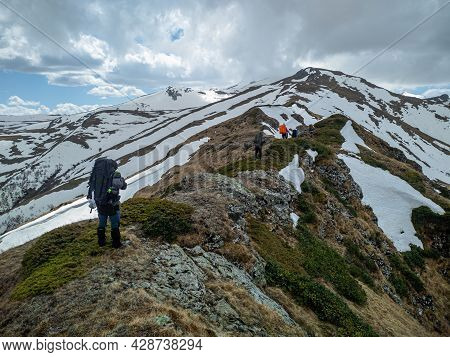 A Group Of Tourists With Backpacks Moves Along A Mountain Range, Partially Covered With Snow. Hiking