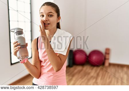 Young brunette teenager wearing sportswear holding water bottle hand on mouth telling secret rumor, whispering malicious talk conversation