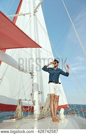 Joyful young man standing on board of his yacht in sea or ocean. Luxury boat. Guy wear shorts, shirt and glasses. Concept of sailing vacation or tourism. Summertime. Sunny daytime