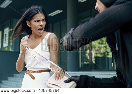 Robber want to steal handbag of angry girl. Male bandit wear black hoodie and threatening with pistol to young european brunette woman. Concept of robbery. City daytime