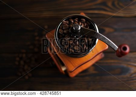 Coffee Mill On A Wooden Table In A Rustic Style. Coffee Beans In A Manual Coffee Mill On A Rustic Ta