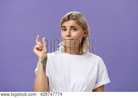 Girl Having Tiny Problem. Concerned Attractive Blonde Girl With Tattoo On Arm Pursing Lips In Troubl
