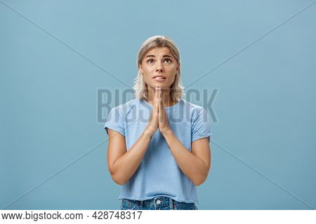 Studio Shot Of Hopeful Focused Dreamy Girl With Attractive Face And Blonde Hair Holding Hands In Pra