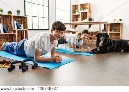 Young caucasian couple smiling happy training abs exercise with dog at home.