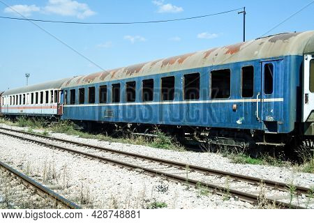 Old And Rusty Abandoned Passenger Wagons, Carriage Car, Lost And Let To Rot In A Closed Train Statio