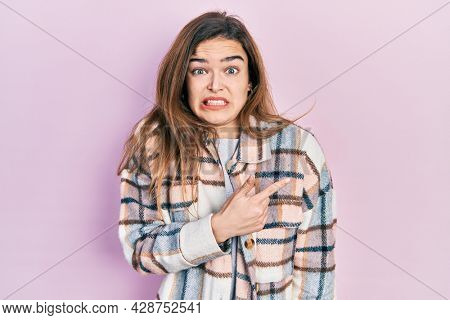 Young caucasian girl wearing casual clothes pointing aside worried and nervous with forefinger, concerned and surprised expression
