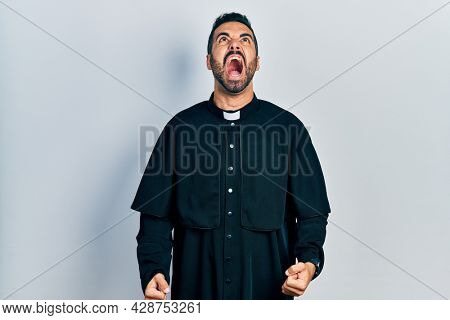 Handsome hispanic man with beard wearing catholic priest robe angry and mad screaming frustrated and furious, shouting with anger. rage and aggressive concept.