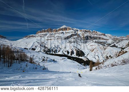 View of a ski resort piste with people skiing in Dolomites in Italy. Ski area Arabba. Arabba, Italy