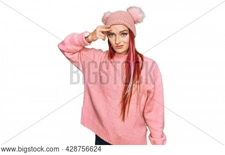 Young caucasian woman wearing casual clothes and wool cap pointing unhappy to pimple on forehead, ugly infection of blackhead. acne and skin problem