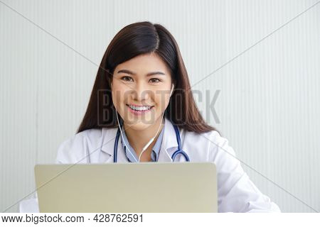 Asian Female Doctor Online Video Call Check The Symptoms With The Patient Via The Internet. On A Lap