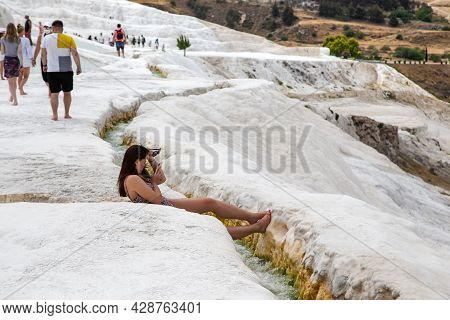 Pamukkale, Turkey - 1 June, 2021: An Unidentified Young Woman Rests On A Slope Covered With Limeston
