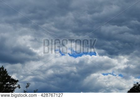 A Fragment Of The Sky Covered With Thick Rain Clouds With A Glimmer Of Blue Sky.