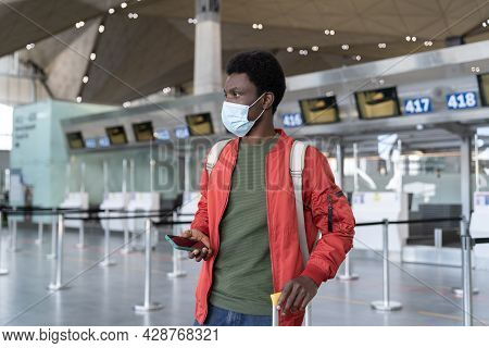 Young Black Male Traveler In Airport Wait For Flight Use Smartphone Wear Mask In Covid-19 Epidemic.