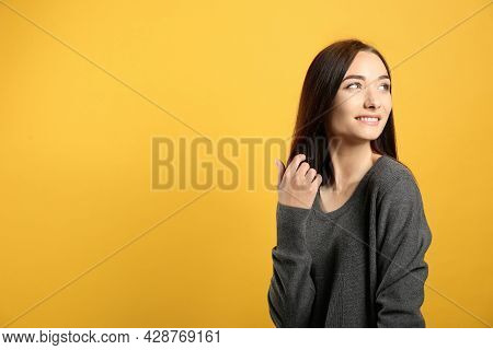 Portrait Of Pretty Young Woman With Gorgeous Chestnut Hair And Charming Smile On Yellow Background,
